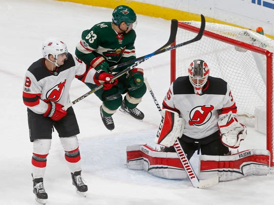 Minnesota Wild's Tyler Ennis, center, jumps to clear the way for a shot on New Jersey Devils goalie Cory Schneider in the second period of an NHL hockey game, Monday, Nov. 20, 2017 in St. Paul, Minn. (AP Photo/Jim Mone)