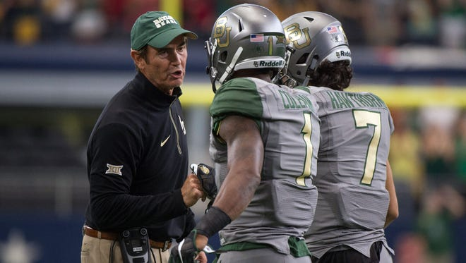 Art Briles speaks to two of his players during his time as Baylor's coach.