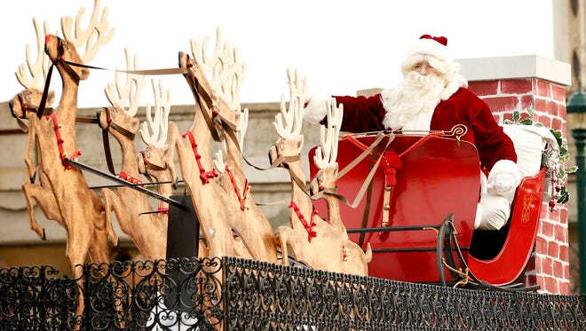 Waving to thousands of spectators, Santa brings up the rear of the 2015 Downtown Elmira Holiday Parade.