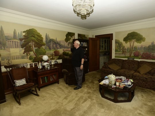 Tom Hoffert shows the mural painted on his living room wall at his Cleveland Avenue home in Fremont.