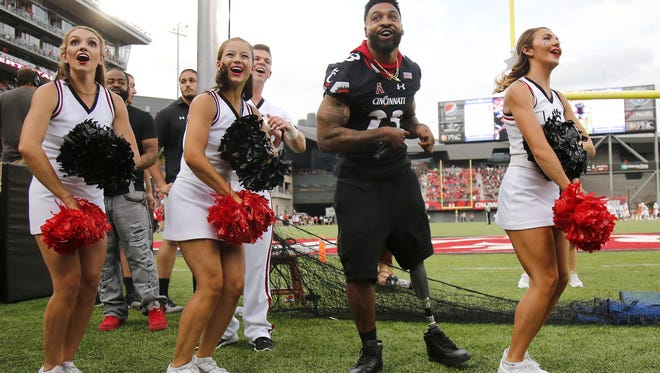 Former Cincinnati Bearcats running back Isaiah Pead leads the student section in a pre-game cheer before a 2017 UC game. Pead is setting his sights on a gold medal in the 2020 Summer Paralympic Games.