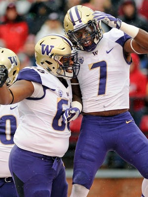 Washington linebacker Keishawn Bierria (7) and defensive lineman Damion Turpin (66) celebrate a sack against Washington State during the first half Friday in Pullman, Wash.