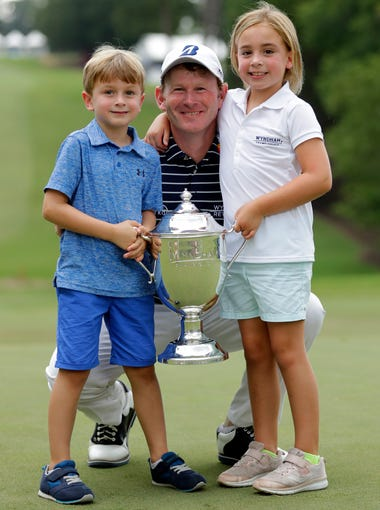 Brandt Snedeker, center, poses with the trophy and