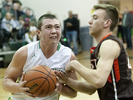 Floyd Central Highlanders guard Luke Gohmann drives as Columbus East Olympians guard Zach Sanders tries to get a hand on the ball.  February, 2016