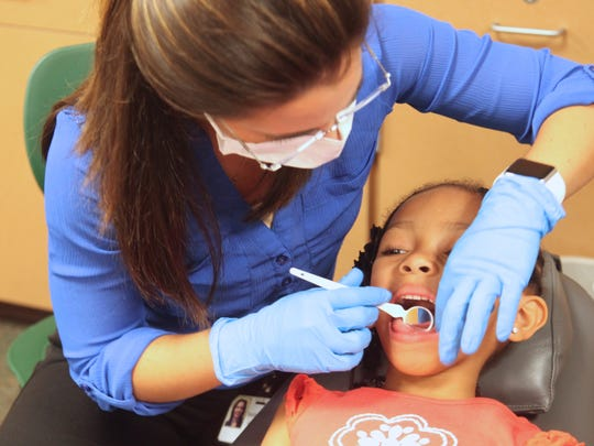 Jahyani Smiley, 5, receives a free dental exam from Dr. Maidelys Oliva during the Annual Omega Family Health Forum at Dunbar High School on Saturday.
