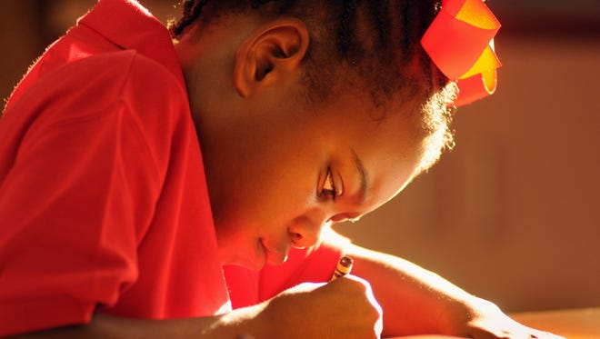 First grader X'Zaileya Register concentrates on her art work at Riviera elementary in Palm Bay.