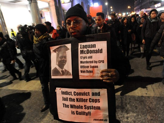 A man holds a sign during a protest for 17-year-old Laquan McDonald early Nov. 25, 2015, in Chicago. Protests continue against the actions of Chicago police officer Jason Van Dyke, who shot McDonald 16 times last year.