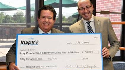 Inspira Health Network President and CEO John DiAngelo (left) presents Dr. Robin Weinstein of the M25 Coalition with a $50,000 check to support the Cumberland County Housing First Collaborative.