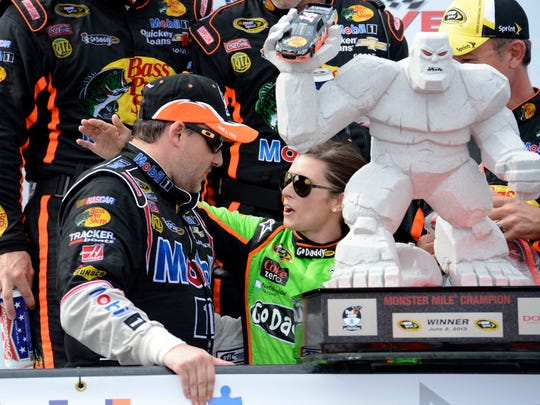 Tony Stewart, left, meets with Danica Patrick, in Victory Lane after Stewart won a NASCAR Sprint Cup Series race, June 2, 2013, at Dover International Speedway in Dover, Del.