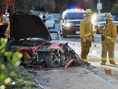 First responders gather evidence near the wreckage of a Porsche sports car that crashed into a light pole on Hercules Street near Kelly Johnson Parkway in Valencia on  Nov. 30, 2013. A publicist for actor Paul Walker says the star of the