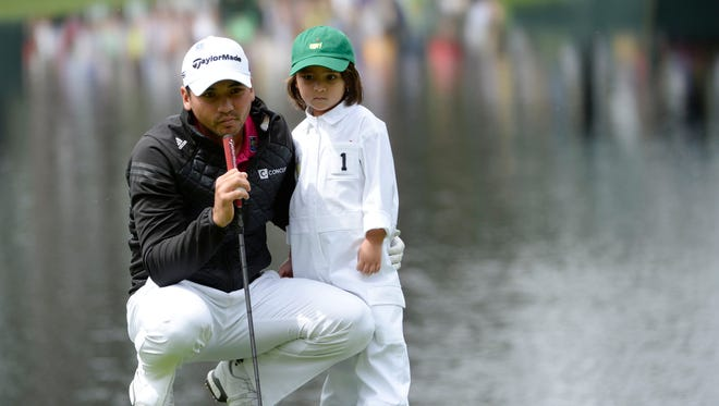 Jason Day with son Dash Day on the 4th green during the Par 3 Contest prior to the 2016 Masters.