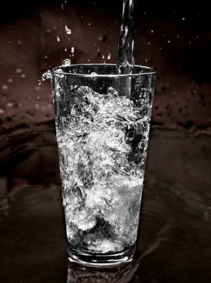 A photo illustration of water being poured into a glass.