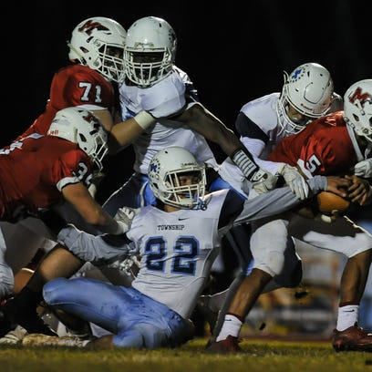 Freehold Township's Artie Bader (#22) tries to rip