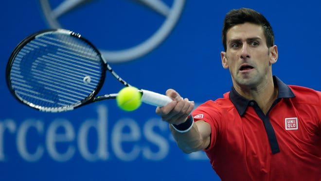 Novak Djokovic of Serbia reaches for a shot as he plays against Zhang Ze of China during their singles match of the China Open.
