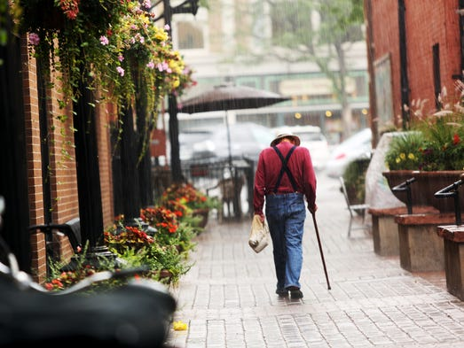 A man walks through the rain at Trimble Court in Old Town Friday, July 18, 2014. City Council passed an ordinance updating the Old Town Historic District design standards.