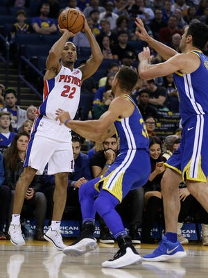 The Detroit Pistons' Avery Bradley shoots against the Golden State Warriors' Stephen Curry on Sunday night.