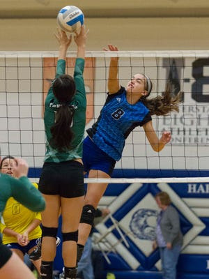 Charley Andrews of Harper Creek spikes the ball against Pennfield.