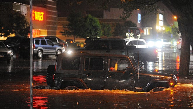 A motorist navigates high water at 43rd Street and Kelley Avenue near Target in The Empire East after heavy rain last year.