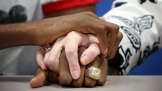 Aaron Pryor III, Aaron Pryor Jr., and Frankie Pryor hold hands as they share memories of Aaron Pryor during Monday's press conference at the Golden Gloves boxing gym in Over-the-Rhine. Pryor passed away at home Sunday surrounded by his family after a long battle with heart disease.