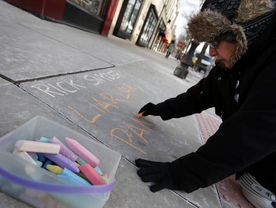 Susan Fecteau, 58, of Ann Arbor, writes a message in