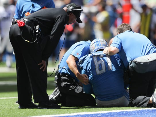 Lions coach Jim Caldwell checks on defensive lineman