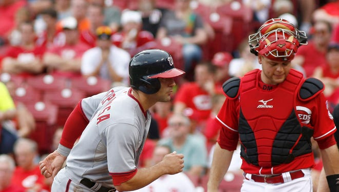 Washington Nationals second baseman Danny Espinosa (8) tags up at home past Cincinnati Reds catcher Devin Mesoraco (39) after being walked in during the fifth inning at Great American Ball Park.