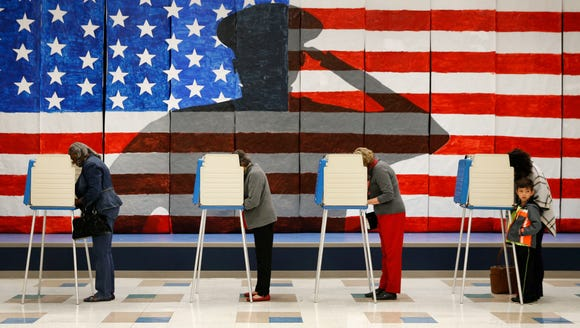 Voters line up in voting booths to cast their ballots