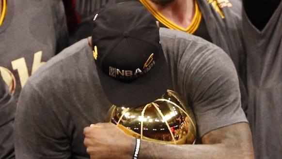 LeBron James cradles the Larry O'Brien trophy after