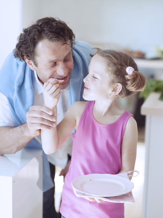 Young girl feeding her father