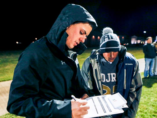 Athletic trainer Austin Mueller evaluates a youth football