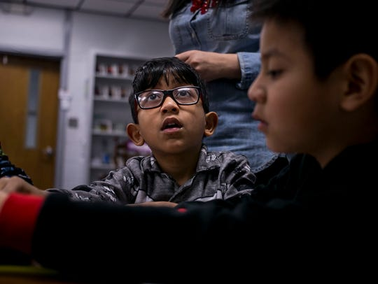 Aniket Nijil, 5, looks up as he colors with classmates