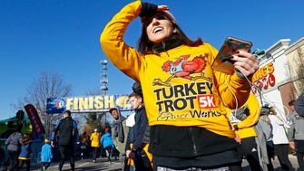 Ashlan Fulare looks for friend to make it to the finish line during the TurkeyTrot 5K, Thursday, Nov. 23, 2017, in Nashville, Tenn.