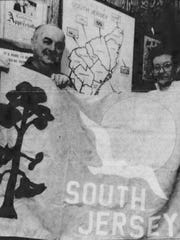 Bettsey Arnold (right) sewed together a proposed state flag for an independent South Jersey state. Arnold, then-Seaside Heights borough clerk, is also seen here in this 1986 photo in front of a map of the would-be 51st state (this 1980s-version includes Monmouth County). Then-Seaside Heights Mayor George E. Tompkins (left) was the leader of the South Jersey secessionist movement in Ocean County.