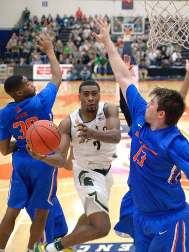 Michigan State forward Javon Bess, center, shoots as