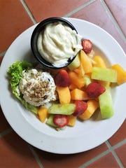 Rafferty's house Sunshine Chicken Salad is served topped with candied pecans and sides of fresh fruit and fluffy sweet orange dressing.