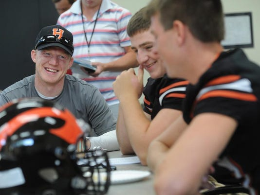 Hanover assistant coach Zac Carrick and players Bailey Kenworthy and Kyle Krout laugh during YAIAA media day Monday at the York Daily Record offices.