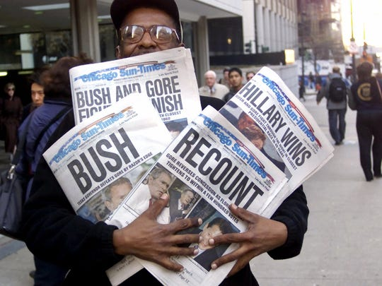 FILE - In this Nov. 8, 2000 file photo, Willie Smith holds four copies of the Chicago Sun-Times, each with a different headline, in Chicago, reflecting a night of suspense, drama and changes in following the presidential race between Vice President Al Gore and Texas Gov. George W. Bush. What happens if America wakes up on Nov. 9 to a disputed presidential election in which the outcome turns on the results of a razor-thin margin in one or two states, one candidate seeks a recount and the other goes to court? (AP Photo/Charles Bennett, File)