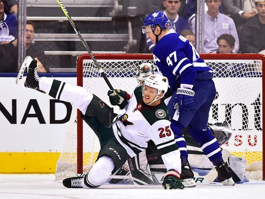 Toronto Maple Leafs center Leo Komarov (47) knocks down Minnesota Wild defenseman Jonas Brodin (25) in front of Wild goalie Devan Dubnyk during the first period of an NHL hockey game Wednesday, Nov. 8, 2017, in Toronto. (Frank Gunn/The Canadian Press via AP)