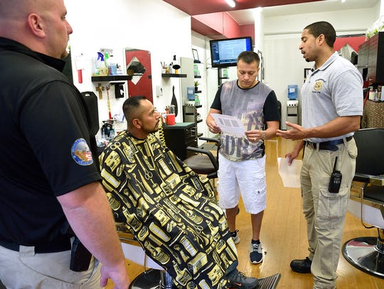 Englewood police Detective Miguel Sanchez, right, and