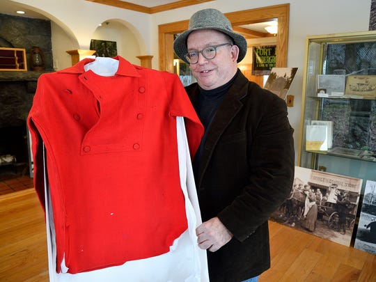 Tom Meyers, Executive Director of The Fort Lee Museum, holds a firemen's uniform designed by Maurice Barrymore, John Barrymore's father.