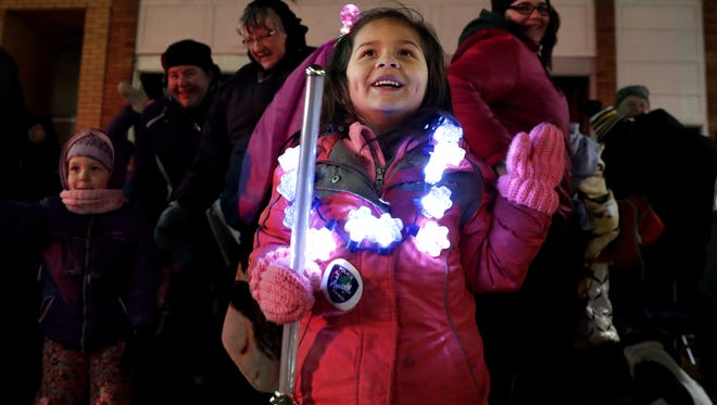 Children will again be dazzled Tuesday by the wonders of the Downtown Appleton Christmas Parade. Here, Janessa Melchert, 4, waves to Santa Claus as he makes his way down College Avenue during last year's parade.