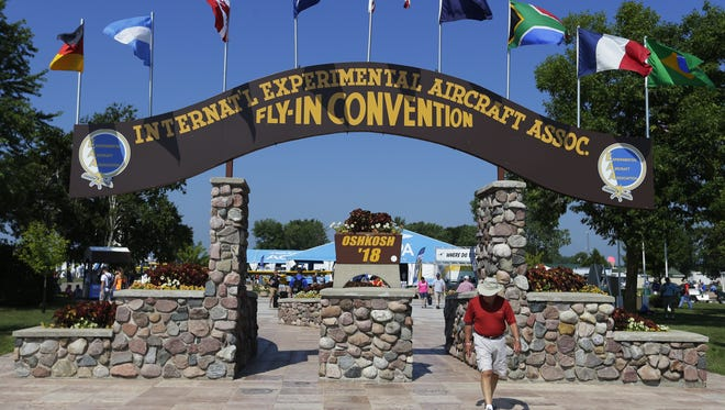 The Experimental Aircraft Association AirVenture fly-in convention arch is an icon as people pass to get to the flightline,Tuesday, July 24, 2018, at Wittman Regional Airport in Oshkosh, Wis.