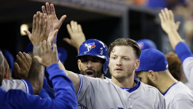 Toronto Blue Jays' Josh Donaldson receives high-fives in the dugout after scoring against the Detroit Tigers during the eighth inning of a baseball game Friday, July 3, 2015, in Detroit. (AP Photo/Duane Burleson)