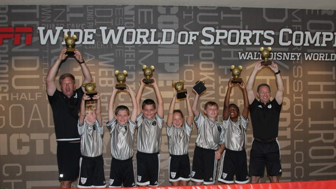 From left to right: David Harkins, David Harkins II, Ben McGovern, Dylan McGovern, McKenzie Watson, Gavin Core, Mason Tucker and Bryan Watson of Matrix Soccer celebrate their 3v3 title at Walt Disney World.