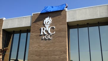 College officials unveil the new logo for Rowan College of Gloucester County during a ceremony July 1. The name change stems from a partnership between Gloucester County College and Rowan University. The agreement was signed in January and promises greater accessibility and affordability for students.