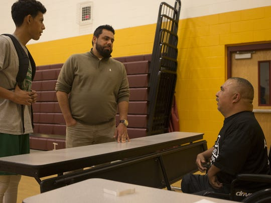 David Solano, right, talks with Eddie Martinez, center, and Eddie Martinez, Jr. after Solano's No Limit Hoops at Raul H. Castro Middle School in February.
