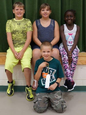 Carson Raines, Harrisanna Ely, Jusby Batekila and Kayden Wingate (center front), all fifth-graders at Florence Elementary, placed at the Boone County 4-H & Utopia Fair for their produce. Carson placed second for his Largest Pumpkin and Most Unusual Vegetable.  Harrisann placed second for Largest Watermelon and Jusby placed first for her Largest Watermelon.  The final grower, Kayden Wingate, placed third for his Largest Pumpkin.  The students planted their crops in May with Science Club on the UK extension property across from Central Park.