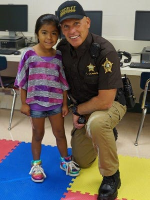"""Krystal DeLeon, a first-grader at Florence Elementary, posed with the School Resource Officer (SRO) Chris Combs on the first day of school. Combs was connecting with the students and """"pounding the rock,"""" spreading the love and respect that exploded with each pound."""