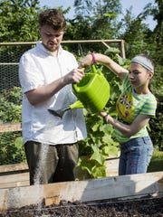 Christopher Pensiero, a teacher at The Bancroft School in Haddonfield, and student Sydney Kaplan grow herbs in the on-campus horticultural center.