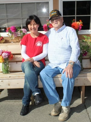 """Al Cooper and Judi Lee sit in front of the """"Little Apple Deli"""" in Manzanita, Oregon drawn together by shared connection to the land of her birth."""